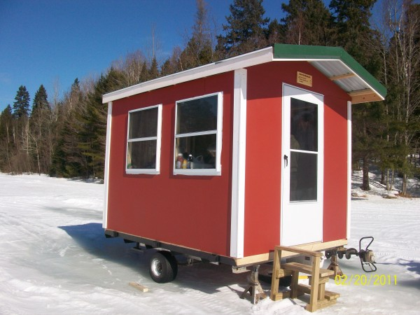 MY SHACK IS BUILT ON A 2 PLACE SNOWMOBILE TRAILER, IT IS SHAPED LIKE A HOUSE, WITH AN OVERHANG OVER THE DOOR, NEW WINDOWS AND DOORS, AND A PEAKED METAL ROOF.