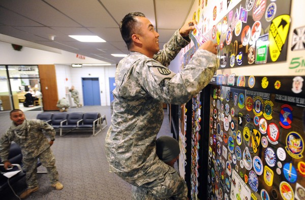 Sgt. Jake Garcia puts a sticker of his unit onto the wall as he sits oon the shoulders of Spc. Andre Varea at the Bangor International Airport New Year's Eve 2010. They are among the 117 membes of the Hawaii Army National Guard 230th Engineer Company that made a stop in Bangor on their way home from Afghanistan.  They hope to arrive in Hickman, Hawaii sometime in the morning on January 1st 2011. (Bangor Daily News/Gabor Degre)