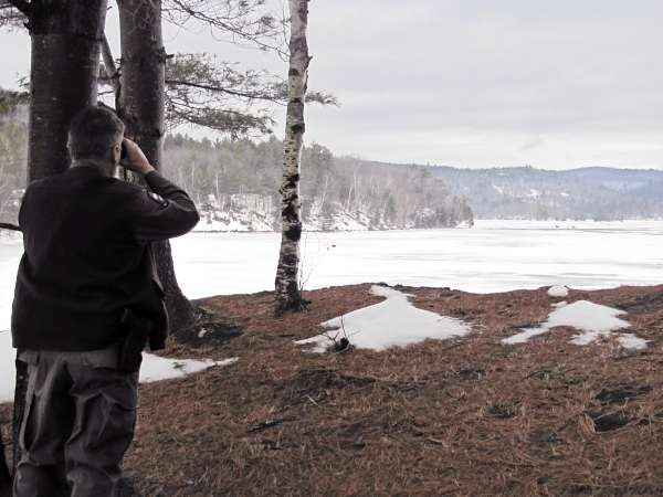 028: Game Warden Rick Clowry hides in a stand of pines as he watches a group of ice fishermen tend to a flag Saturday, January 1, 2011 on Wyman Lake in central Somerset County. Performing surveillance prior to approaching a group of fishermen is one of the methods Clowry uses to catch people fishing illegally. (Bangor Daily News/Christopher Cousins)
