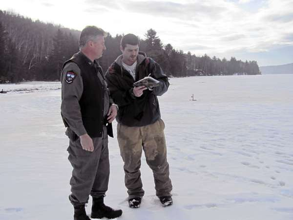 005: Brandon Knox of Benton, right, signs a ticket for a bag violation Saturday, Jan. 1, 2011, on Wyman Lake in central Somerset County. Game Warden Rick Clowry, left, found Knox in possession of two splake longer than 14 inches. Under Maine law, the daily limit on splake is one fish between 12 and 14 inches, and one larger than 14 inches. (Bangor Daily News/Christopher Cousins)