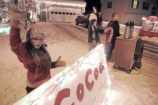 CAPTION Abby Sargent, 7, holds up the family's billboard as she and her family waves to attract passing motorists so they can offer hot chocolate in front of her family's home on 47 Bowdoin Dr.--off North Main St. in Brewer Saturday night. Abby and her sisters Jessica Sargent, 9, Torri Openshaw (cq), 8, and cousin Jaclyn Cyr (cq), 11 of Holden recently started a hot chocolate concession there to raise money for the Cystic Fibrosis Foundation and for the medical treatment their family friend , Brock Blanchard, 3, son of Rebecca and Chad Blanchard of Mt. Desert, ME. Until  Christmas, the young ladies hope to be in their front yard on Thursday, Friday and Saturday nights from 5:30-- serving hot chocolate to passing motorists and others. So far approximately  100 people have donated $200 to their cause and they said they hope to raise $1000 before Christmas. (Bangor Daily News/John Clarke Russ)    (WEB EDITION PHOTO)