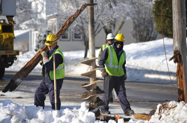 Mike Apt of Kenduskeag carries part of a utility pole that was snapped when a public works plow truck slid off an icy section of Mount Hope Avenue and splintered the pole near Fruit Street School in Bangor around 8 a.m. Monday, Jan 3, 2011.  Walking on the right was fellow Bangor Hydro lineman Dan Auxier of Veazie. Bangor Hydro Electric Company and Bangor Natural Gas workers as well as Bangor Police responded. There was no disruption of power to the school or neighborhood. A 100-yard section of Mount Hope Avenue was closed until the pole was replaced . (Bangor Daily News/John Clarke Russ)