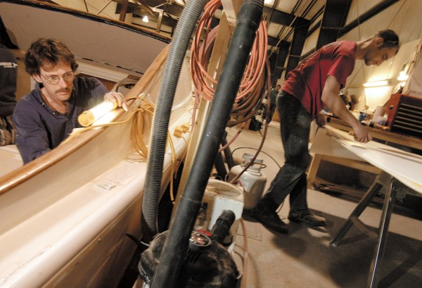 Carpenters Mike Smith (left) of Jonesboro and Joel Dolbow of Brewer work on a 29-foot Runabout jet boat at the Hinckley Co. boat division in Trenton. Hinckley's Trenton facility, constructed during a 1998 expansion, allows a shorter commuting time for workers such as Dolbow and Smith. Their current commute to the Trenton facility takes half the time of the commute to Hinckley's older Southwest Harbor facility and allows them to live in areas more affordable than on Mount Desert Island.   BANGOR DAILY NEWS PHOTO BY JOHN CLARKE RUSS