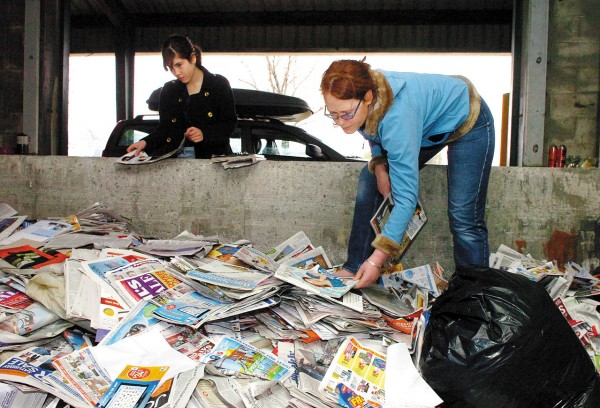 Bangor residents Grace Stern (right) and her daughter Marshelle Stern wade through recycled newspapers and magazines looking for ones that they can reuse at the recycling drop-off center on aine Avenue in Bangor on Wednesday. Teh city is researching possible changes to its recycling and santitation policies in order to save money and encourage more resident to recycle.  (BANGOR DAILY NEWS PHOTO BY BRIDGET BROWN)