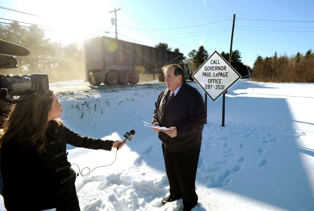 Carmel Town Manager Tom Richmond holds a press conference along Route 2 near one of four new signs he has authorized to be posted. The signs encourage motorists to call Governor LePage's office if they want to complain about the miserable road conditions along the main road that runs thorough the town. BDN Photo by Kevin Bennett