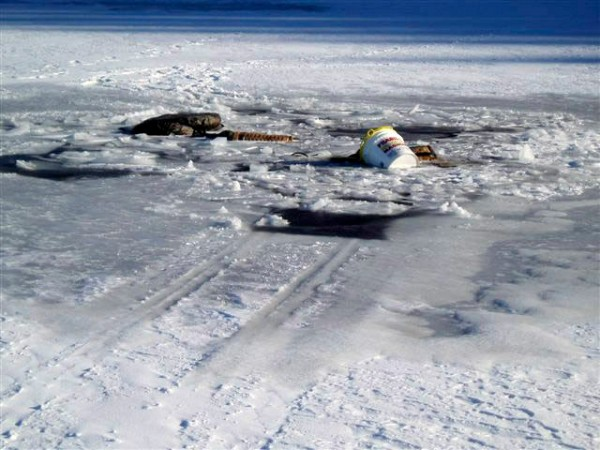Items belonging to three ice fisherman lay on top of thin ice on Long Lake in northern Maine. The men went through the ice on an ATV and tote sled Thursday morning. All got out safely. credit Maine Warden Service