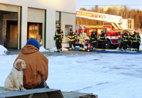 STAND-ALONE PHOTO:  Bangor Armor Liners employee Neil Morrill sits his his girlfriend's dog, Blossom, as they watch Bangor firefighters mop up a furnace fire at the Outer Hammond Street shop on Thursday afternoon, January 6, 2010. (BDN photo by Kevin Bennett)