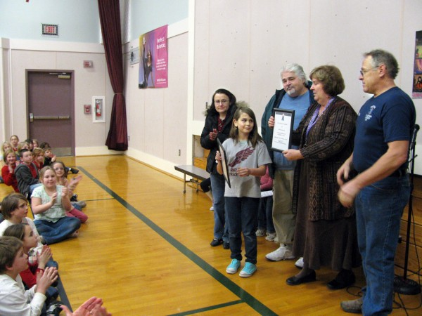 Students at the Edna Drinkwater School in Northport applaud as their classmate, Julia Cerone, 10, was honored Thursday, Jan. 6 by the Northport Volunteer Fire Department for bravery during a Christmas Eve fire that destroyed her home. Julia and her cousin, Diana Tyutyunnyk, 13, of Orono, helped to save Diana's  two-year-old sister and their grandmother, who was badly burned in the blaze. Bangor Daily News/Abigail Curtis