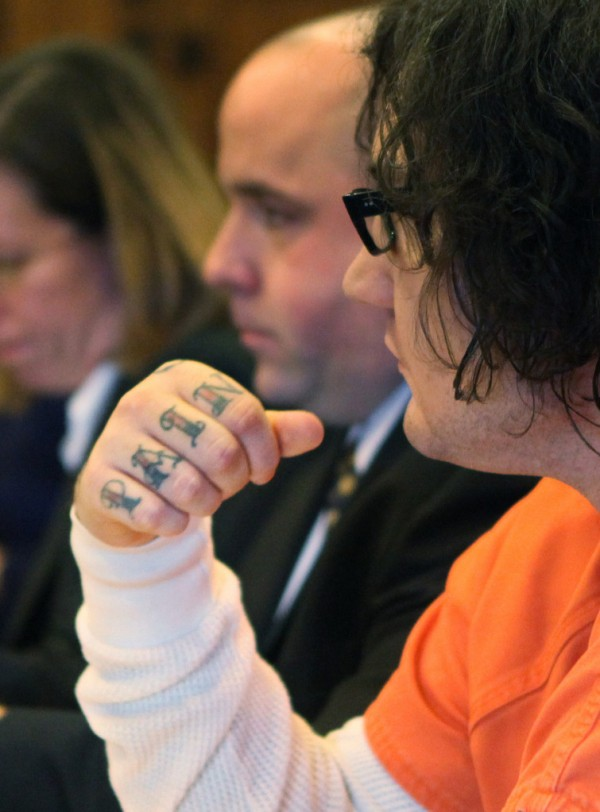 A tattoo on Chad Gurney's knuckles is seen Monday, Jan. 10, 2011 in Portland, Maine as he sits during his trial on charges of strangling his girlfriend 18-year-old Zoe Sarnacki then cutting off her head and setting her body on fire. Prosecutors are saying a 29-year-old Portland man was not insane when he strangled his girlfriend, cut off her head and set her body on fire nearly two years.  But defense attorney Sarah Churchill told a judge during Monday's opening statements that Chad Gurney was suffering from a mental disease or defect that prevented from appreciating the wrongfulness of his actions.  (AP Photo/Joel Page)