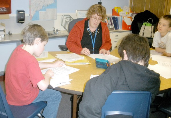 Teacher Linda Dunn reads along with members of the Downeast School third-grade after school club as they rehearse their lines for readers' theater. (BDN photo by Joni Averill)