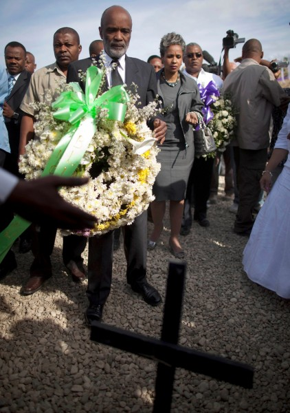 Haitian President Rene Preval, center, Haiti's first lady Elisabeth Debrosse Preval fourth from left, and Haiti Prime Minister Jean-Max Bellerive, right,  carry wreaths for the victims of the Jan. 2010  earthquake during a religious ceremony at the Titanyen mass grave site on the outskirts of  Port-au-Prince, Haiti, Tuesday, Jan. 11, 2011. The religious ceremony is one of many events planned to mark the one-year anniversary of the Jan. 12th magnitude-7.0 quake that killed more than 220,000 people and left millions homeless.(AP Photo/Ramon Espinosa)