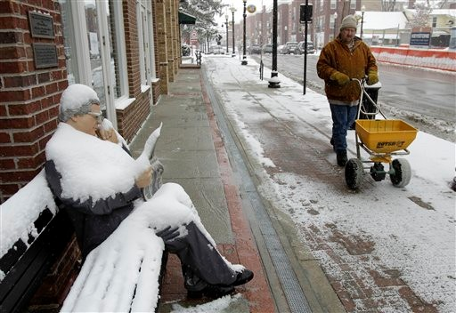 A statue of a man reading a newspaper on a bench is covered in snow as a worker salts sidewalks along Main Street in Carmel, Ind., Tuesday, Jan. 11, 2011. (AP Photo/Michael Conroy)