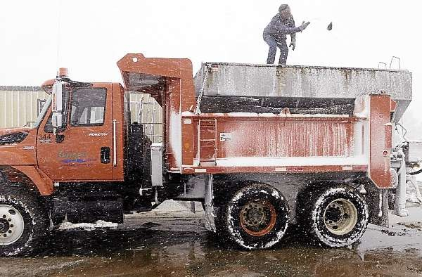 Jeff Sasso of Carmel, a truck driver for Bangor Public Works,  stood atop a department truck to remove hot top that was inadvertently mixed in with the sand payload. He was preparing the truck for another sand load to apply to nearby roads during Wednesday's snowstorm. BPW workers were busy Wednesday plowing area roads as well as hauling sand and road salt from their facility of Maine Ave. in Bangor.  (BDN photo by John Clarke Russ)