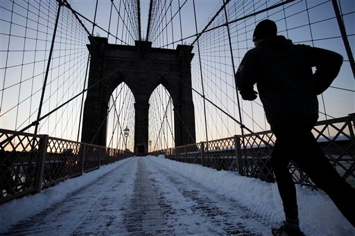 A jogger crosses the Brooklyn Bridge after a snow storm hit the city, Wednesday, Jan. 12, 2011 in New York. Plows and salt spreaders hit the streets up and down the East Coast to stem chaos during Wednesday morning's commute as a storm that shut down much of the South churned northward and dumped several inches of wet, heavy snow. (AP Photo/Mark Lennihan)
