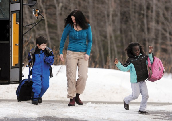 Amanda Logiodice of Pittsfield greets her children on Thursday, January 13, 2011 as they exit the school bus at he familys Pittsfield home. Braeden, left, is Logiodice's biological son and Christella was adopted from Haiti  after the devastating 2010 earthquake. BDN Photo by Kevin Bennett