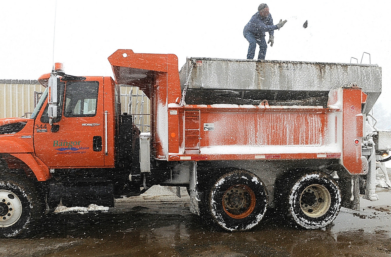 CAPTIONJeff Sasso of Carmel, a truck driver for Bangor Public Works,  stood atop a department truck to remove hot top that was inadvertently mixed in with the sand payload. He was preparing the truck for another sand load to apply to nearby roads during Wednesday's snowstorm. BPW workers were busy Wednesday plowing area roads as well as hauling sand and road salt from their facility of Maine Ave. in Bangor.  (BDN photo by John Clarke Russ)   (WEB EDITION PHOTO)
