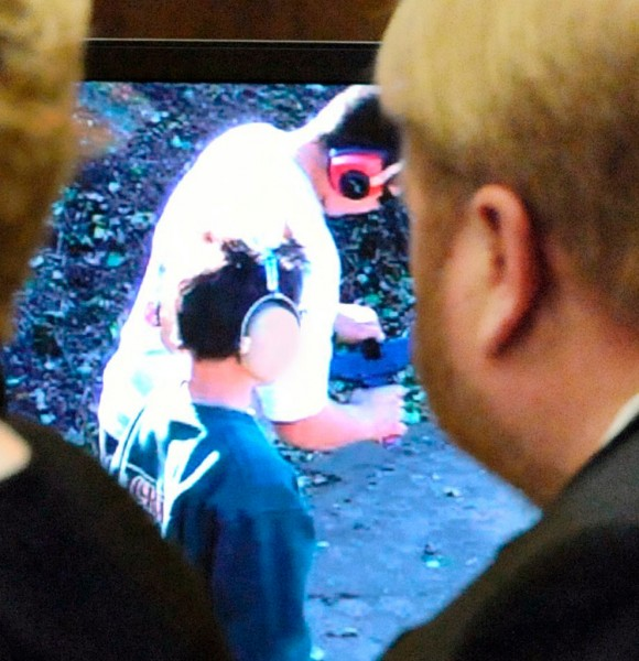 Former Pelham, Mass., Police Chief Edward B. Fleury, right, charged with involuntary manslaughter in the accidental shooting death of Christopher Bizilj, watches a video of Christopher at the gun show where he accidentally shot and killed himself while firing an Uzi during testimony at Hampden Superior Court in Springfield, Mass., Thursday Jan. 6, 2011. The gun show was run by Fleury in October 2008. (AP Photo/Springfield Republican, Michael S. Gordon)