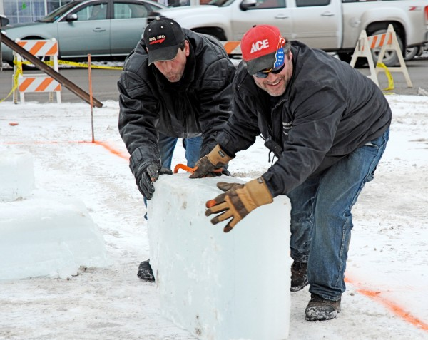 Working together Tim Desjardins (right) and Pascal Plourde maneuver a 400-pound block of ice into place. This weekend ice harvested at Little Black Lake began piling up on the Main Street vacant lot where, with volunteer help, the two men and Pascal's brother Pierre Plourde will construct an ice palace for the World Cup biathlon competitions next month.  Working together Tim Desjardins (right) and Pascal Plourde maneuver a 400-pound block of ice into place. This weekend ice harvested at Little Black Lake began piling up on the Main Street vacant lot where, with volunteer help, the two men and Pascal's brother Pierre Plourde will construct an ice palace for the World Cup biathlon competitions next month.