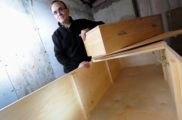 Peter Lindquist, president of Maine Green Casket, stands with a small-scale demo casket and a full-size casket at Gemini Canvas in Rockland where he works. With the help of Robbins Lumber and local cabinet makers, Linquist's &quotgreen caskets&quot-- made of pine and plywood laminate,  are  Maine-made and offer a economical and eco-friendly alternative to other burial and cremation containers. Photographed Friday, Jan. 14, 2011. (Bangor Daily News/John Clarke Russ)