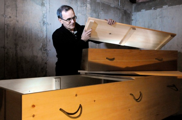 Peter Lindquist, president of Maine Green Casket, shows a small-scale demo casket and a full-size casket at Gemini Canvas in Rockland where he works. With the help of Robbins Lumber and local cabinet makers, Linquist's &quotgreen caskets&quot-- made of pine and plywood laminate,  are  Maine-made and offer a economical and eco-friendly alternative to other burial and cremation containers. Photographed Friday, Jan. 14, 2011. (Bangor Daily News/John Clarke Russ)