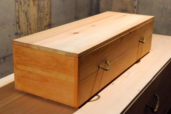 A small-scale demo casket rests on top of a full-size casket. With the help of Robbins Lumber and local cabinet makers, Maine Green Casket president Peter Linquist's &quotgreen caskets&quot-- made of pine and plywood laminate,  are  Maine-made and offer a economical and eco-friendly alternative to other burial and cremation containers. Photographed Friday, Jan. 14, 2011. (Bangor Daily News/John Clarke Russ)