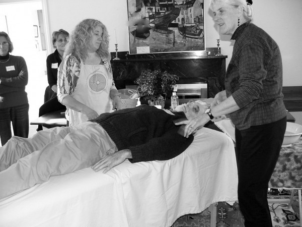 Eva Thompson, left, and Klara Tammany, right, demonstrate how to wash and move a body (demonstrated by Chuck Lakin, on table) for a group of hospice volunteers in April, 2009 in Damariscotta. They are the 3 members of Last Things, a group that provides education about home funerals. (Photo courtesy of Last Things)
