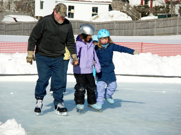 Eight-year-old twins, Skye and Blue Howard of Gouldsboro were seldom off the ice Monday as they took advantage of the holiday to try out the new city ice rink in Ellsworth. Their dad, Bentley Howard, provided extra propulsion as they glided around the rink. BDN photo by Rich Hewitt