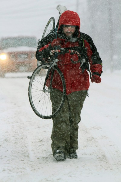 Matthew Calloway carries his bicycle as he walks to work during a snowstorm, Tuesday, Jan. 18, 2011, in Concord, N.H. A mix of snow, sleet and freezing rain iced over roads from Delaware up into northern New England on Tuesday, making for a messy morning commute. (AP Photo/Jim Cole)