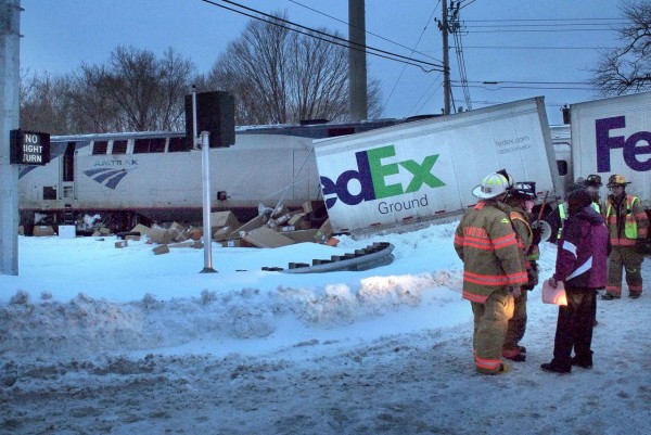 Authorities work the scene where an Amtrak train struck a FedEx delivery truck that became stuck on the tracks Tuesday, Jan. 18, 2010, in Wallingford, Conn. No injuries were reported. A mix of snow, sleet and freezing rain iced over roads from Delaware up into northern New England on Tuesday, making for a messy morning commute. (AP Photo/New Haven Register, V.M. Williams) MANDATORY CREDIT