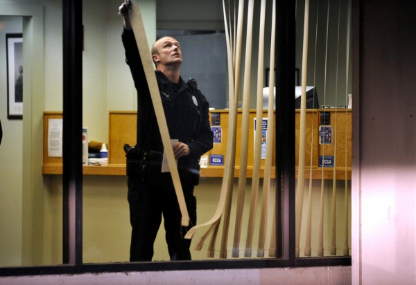 Bangor Patrolman Ed Mercier closes the blinds in the lobby of the Penobscot County Federal Credit Union as detectives combed the scene. He was among the first  police officers on the scene after a robbery was reported there shortly before 4:30 p.m Tuesday. (BDN photo by John Clarke Russ)