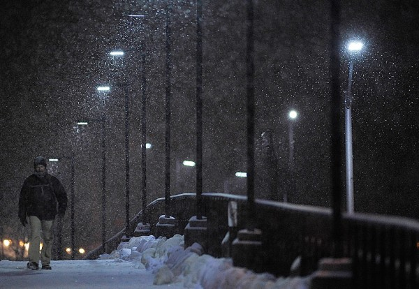 Patrick Mooney of Bangor walks across the Kenduskeag Stream footbridge towards Merchant Plaza as the snow fell late Tuesday afternoon. He braved the storm on his way back from having dinner with his aunt, Teresa Mooney, who also lives in Bangor. (BDN photo by John Clarke Russ)
