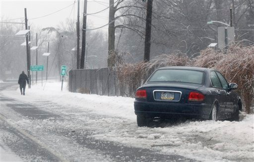 A man walks from his car after sliding off an icy road Tuesday, Jan. 18, 2011, in West Trenton, N.J.  Freezing rain made roads slick throughout the region. (AP Photo/Mel Evans)