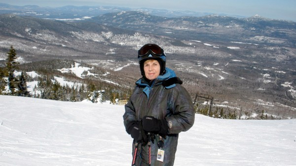 Joni Averill pauses at Sugarloaf with a mountainous panorama behind her.