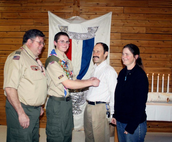During a recent Eagle Scout ceremony, Richard J. Kimball, Jr. was recognized for attaining the top rank in the Boy Scouts of America. Moments after receiving his own badge, Kimball placed the Eagle pin for parents on his stepfather Lou Lainey, while his mother Melanie Lainey and Troop 202 Scoutmaster Jeff Brooks looked on. Photo by Elna Seabrooks/Houlton Pioneer Times