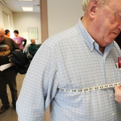 "Gerry Wright is measured by Susan Nile as he was going through the process of signing up for the Biggest Winner weight loss competition at the Maine Central Institute in Pittsfield Friday.  Wright, 76, is the choral director and piano teacher at the school entered because he is hoping to loose 50 lbs.  ""This probably means I have to give up everything I like."" he said.  About 60 people registered for the competition that is originated at MCI, but is open to the public community."