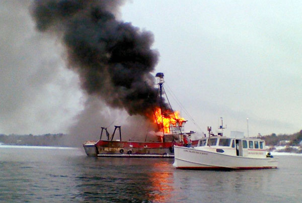 In this photo provided by the U.S. Coast Guard, a fire burns aboard a 67-foot fishing vessel in Casco Bay off Portland on Tuesday. The Coast Guard says the fire was doused by the Portland Fire Department.