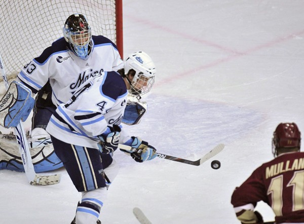 Maine defenseman Ryan Hegarty uses his stick to stop a puck in front of goalie Shawn Sirman while Boston College's Pat Mullane looks on in first-period action Sunday night at Alfond Arena in Orono. Maine knocked off the Eagles 4-1.