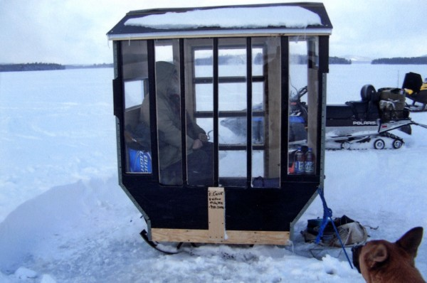 I have two ice shacks. This is the smaller of the two. It is 3 by 4 feet with a cantilever to add more interior space. It is a tag-along with propane heat, Plexiglass windows and is painted black for solar gain. It will seat two in cozy comfort.