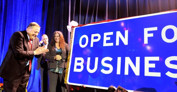 Gov. Paul LePage laughs as Cynthia Rosen (right) and her husband, John Stewart (not pictured), of Washington present him with a road sign during the inaugural reception at the Augusta Civic Center on Wednesday. They raised about $1,300 from fellow supporters and had a Texas company manufacture the sign.
