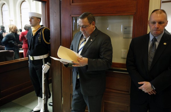 Gov. Paul LePage, center, reviews his notes while waiting to be introduced in the House chamber, Thursday at the State House in Augusta, Maine.  On his first day in office LePage's activities including the swearing in of three new constitutional officers.