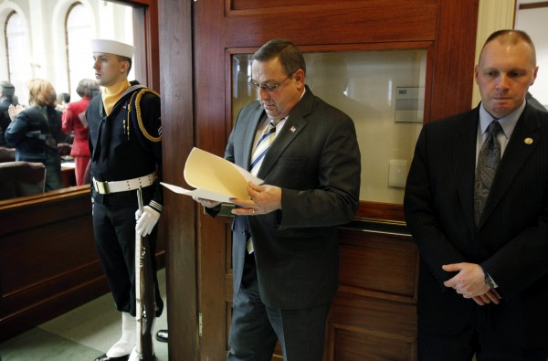 Gov. Paul LePage, center, reviews his notes while waiting to be introduced in the House chamber, Thursdayat the State House in Augusta, Maine.  On his first day in office LePage's activities including the swearing in of three new constitutional officers.