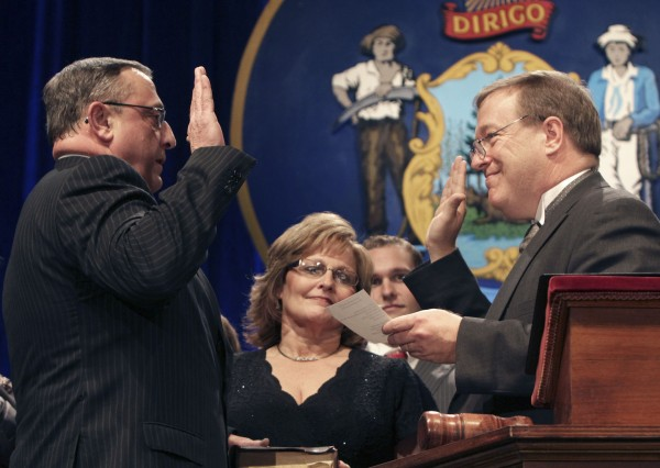 Republican Paul LePage, left, holds his hand on a Bible as he takes the oath of office while being sworn in as Maine's next governor on Wednesday, in Augusta. Holding the Bible is his wife, Ann LePage, and Senate President Kevin Raye, right, administers the oath of office.