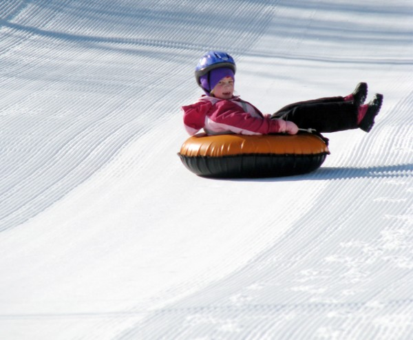 A happy tuber sails down the tubing hill at Camden Snow Bowl.