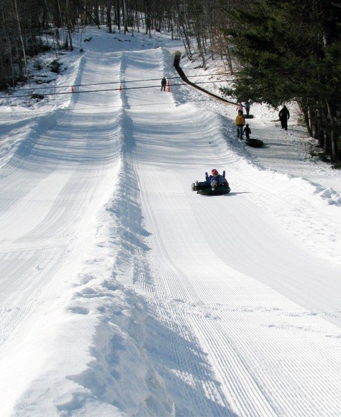 Tubers sail down the tubing hill at Camden Snow Bowl.