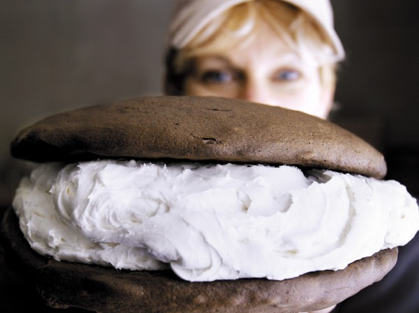 Baker Amy Bouchard holds up a jumbo whoopie pie at her Isamax Snacks factory in Richmond. Bouchard cranks out 5,000 to 7,000 of the desserts per day.
