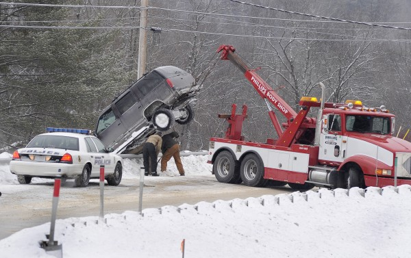 A wrecker tries to remove a vehicle from a guard rail along Rt. 114 in Gorham as this and many other motorists  encountered icy road conditions Tuesday.