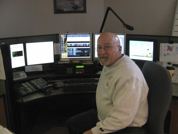 Andy Cardinale, dispatcher at Waldo County Regional Communications Center, poses in front of the bank of computers he uses when emergency 911 and other calls come in.