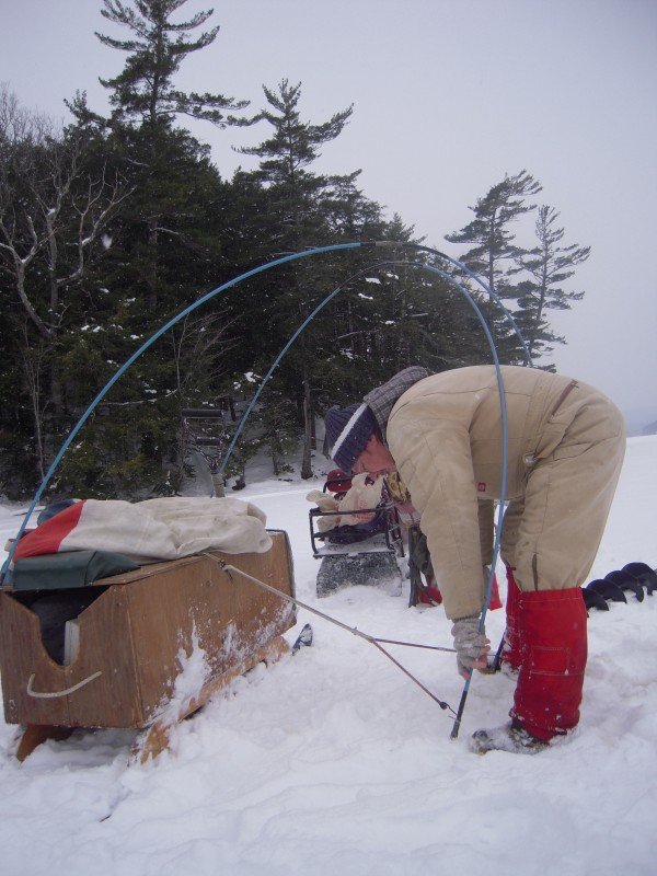 I built this tent myself using old sail cloth and my chimney cleaning poles. Its design allows me to fish anywhere in Maine accessible by snowmobile. The stove in the will heat the shack to 60 degrees even on a bitter day. Note the iPod and speakers to pass the time waiting for flags. The fry pan awaits the first trout of the day, meanwhile the kettle's on. It seats four plus the sled becomes a table for food prep. My &quotshack&quot is unique use of recycled materials providing my family with years of enjoyment.