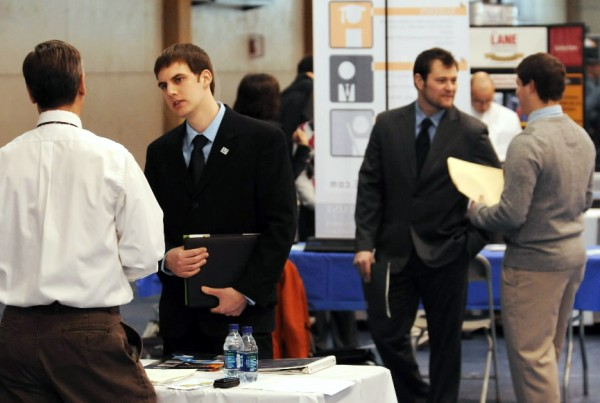 Ben Visvader (second from left), of Willimantic, a University of Maine engineering graduate, talks with David Cynewski (left), of the Portsmouth Naval Shipyard on Wednesday during UMaine's annual Career Fair.