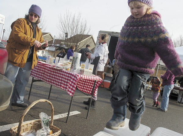 Edie Tierney (right) jumps on coolers during Orono's Winter Farmers Market in January 2008 on Pine Street. Edie's parents, Hanne and Dan Tierney, were vendors at the market, selling local naturally raised meat.